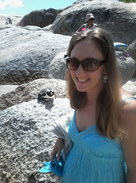 I carefully posed near a penguin at Boulders Beach - note the photobomber above my head, lol