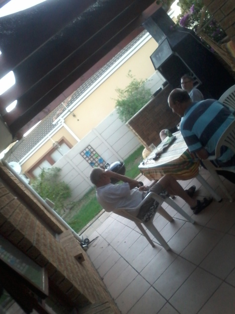 The boys chatting and braai-ing chicken on the Weber