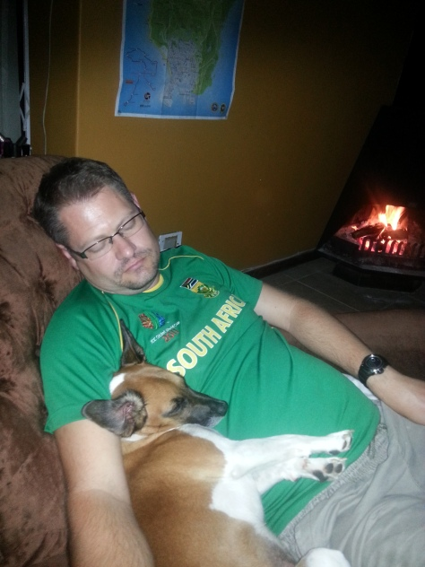 Daddy and baby boy dog relaxing to the gentle sounds of the Band Stand in front of the fire during Earth Hour