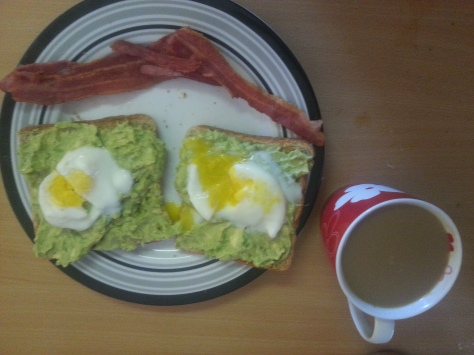 Microwave-poached egg on avo-smeared toast, with a bacon smile (or hat) and coffee on the side
