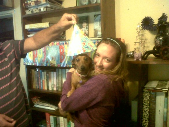 I didn't blog about her birthday last year, but there's my dad holding the birthday hat over her dear little head