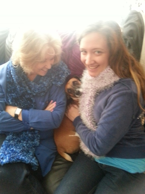 Bertie snuggled between his bescarfed granny and mom