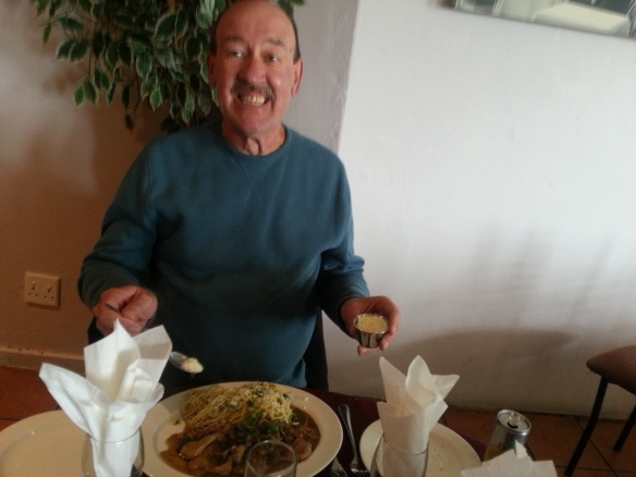 See where I get my standard 'excited about food' photo face from? Here is dad, parmesan cheesing his veal thinghead at the Italian Club