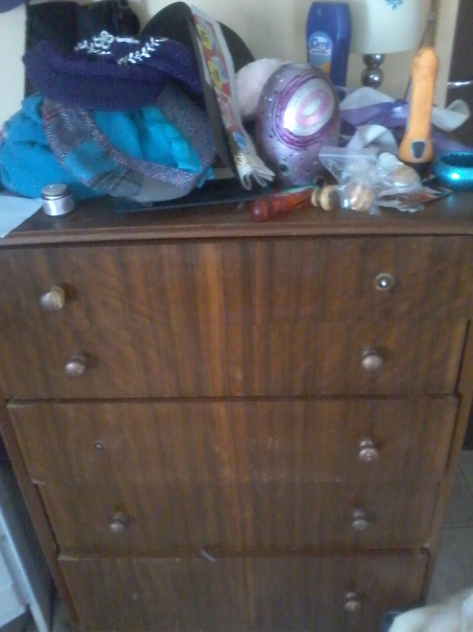 The 'before' shot. Poor thing was missing knobs and had misaligned drawers and its top was used as a general dumping ground.