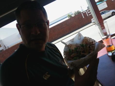 Husband showing me/you/us his basket of crispy tacos with pulled pork filling