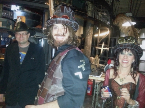 Wedding couple front and centre with my own sweet Husband in his steampunk outfit to the left (yes, that is a silver can opener in his jacket pocket, and a brown Batman teeshirt peeking out from under his suit jacket. With a cowboy/Indiana Jones hat on his head. So steampunk.)