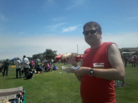 Husband enjoying the sunshine at the doggie show, with a wors roll and warm beer. Happiness is.