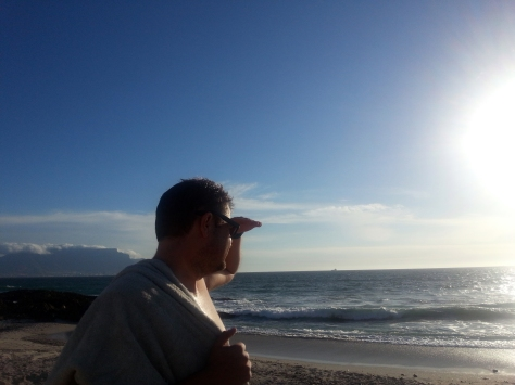 Husband gazing at white hot sun after his dunk in the sea