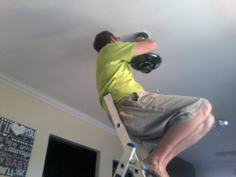 Here is Husband, sitting on the ladder to install the lounge ceiling fan. I watched <i>Love, Actually</i> to distract myself from worrying he would fall off.You can just see the new crystally dining room light fitting at his knee and the new kitchen light behind that