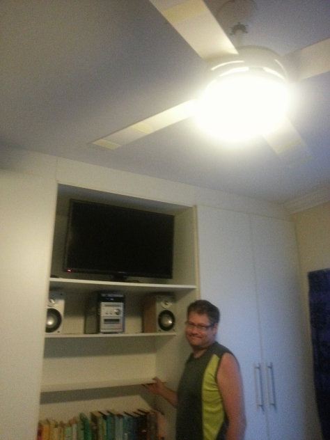 In the main bedroom, Husband replaced ugly light fitting with a ceiling fan, spray painted glow-in-the-dark paint onto its blades in a spiral shape, removed doors from the centre bedroom cupboards, installed TV and hi-fi AND used bits of the cupboard doors he removed to make new shelves. He deserves to look proud!