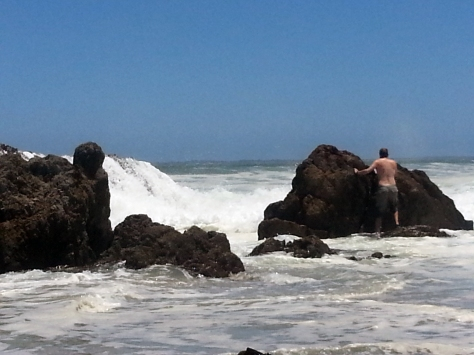 Husband hiding from the crashing waves by placing himself behind a large rock