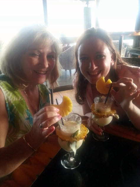 Mum and me with our very pineapple-y pina coladas. Note there's a pineapple slice in the glass, a thick wedge around it, and a slice garnishing the top.