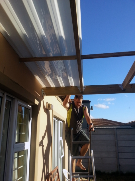 On with the patio installation! Here is Husband, climbing down the ladder after securing the first length of opal white covering