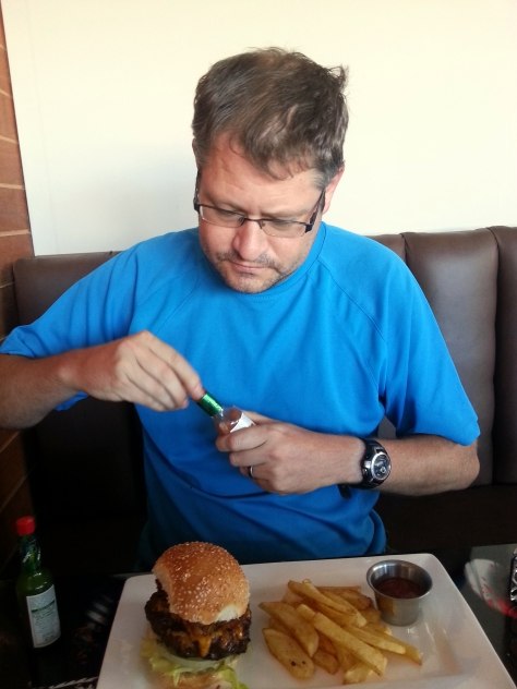 Here is Husband, saucing up his Red Hot Chili burger