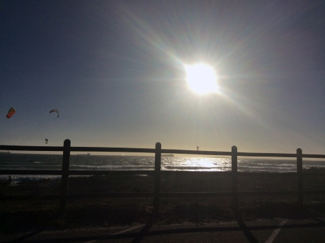 Beautiful bright white sun and some kite surfers in the left of the shot