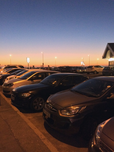 The almost-as-lovely-as-Friday's sunset on Saturday - the sea is just beyond the row of cars, under the streetlamps