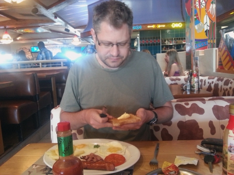And here is Husband with his breakfast - he always gets an extra cheese griller, and the huge Tabasco sauce bottle