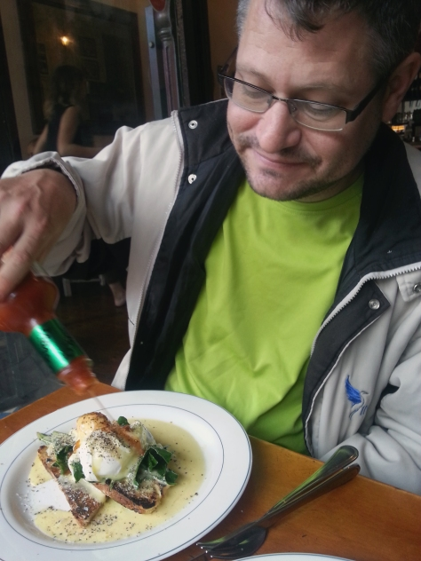 Husband happily Tabasco-saucing his well-peppered eggs ben.