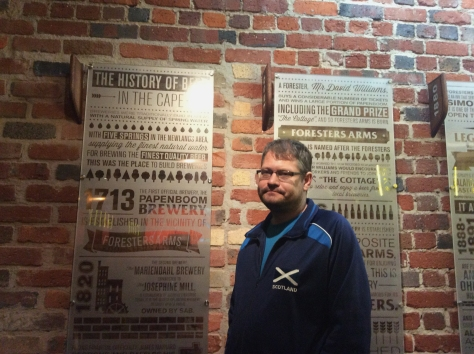 Husband not-so-happy about being made to  pose at the 'History of beer in Cape Town' walls in the beer-tasting room.