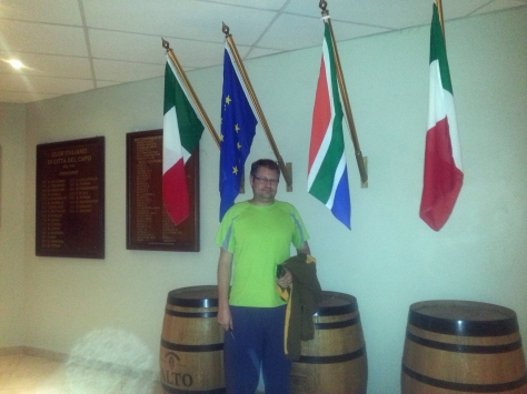 Husband at the wall of barrels and flags inside the Italian Club.
