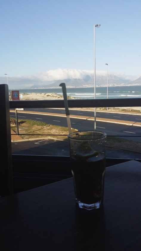 Look at Husband's lovely lemony breakfast Cola against a backdrop of tableclothed Table Mountain. This was at Primi, Blouberg.