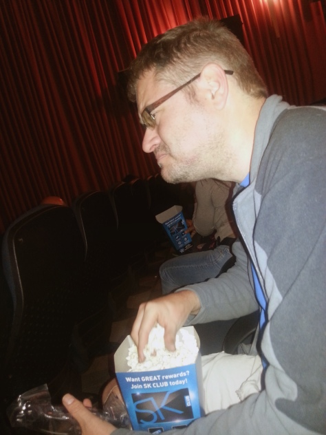 Husband enjoying his popcorn in the cinema. It's just not the complete movie experience without over-salted popcorn that makes you cough.