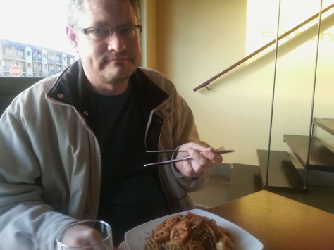 Here is Husband, brandishing his utensils as though they're chopsticks. He had the seafood stir fry noodles.
